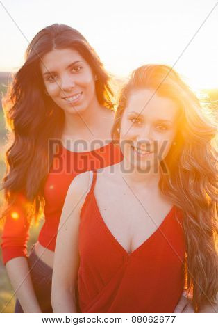 Two girls walking in the countryside with a nice reflection of the sun