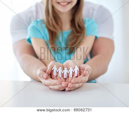 people, charity, demography and family  concept - close up of father and girl holding cutout human in cupped hands at home