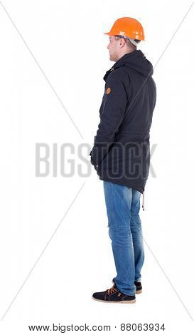 Back view of an engineer in  construction helmet stands.  Standing young guy in parka. Rear view people collection.  backside view of person.  Isolated over white background.