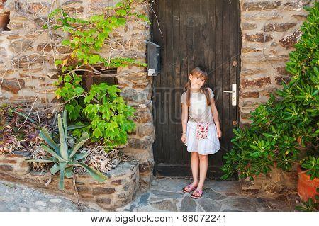 Summer portrait of a cute little girl, standing next to old wooden door