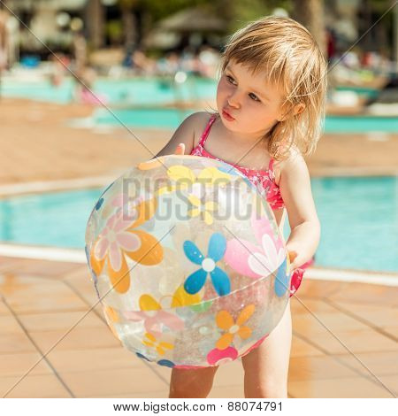 little cute girl playing near the pool with a ball