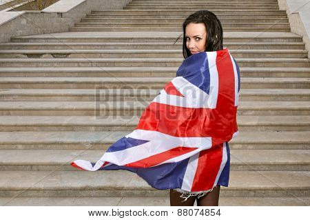 Young women with Union Jack flag against stairs