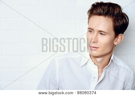 Portrait of a smiling handsome young man in white shirt.