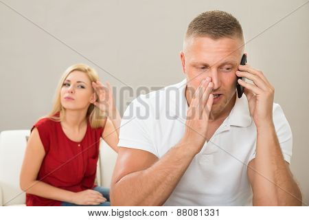 Wife Looking At Husband Talking On Mobile Phone