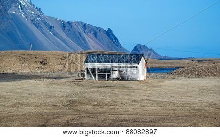 A solitary farm house stands on the vast grass fields in a farm in Stokksness, on the southern coast of Iceland.