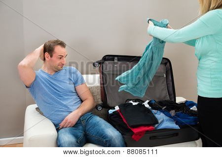 Man On Sofa While Woman Folding Clothes