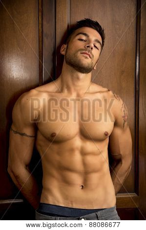 Sexy handsome young man standing shirtless against wooden wardrobe