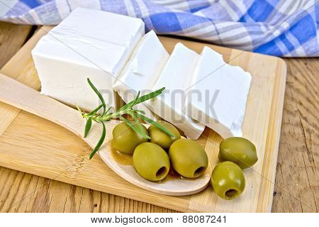 Feta with olives and rosemary in spoon on board