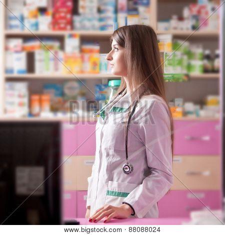 Pharmacist Looking Away At Her Working Desk