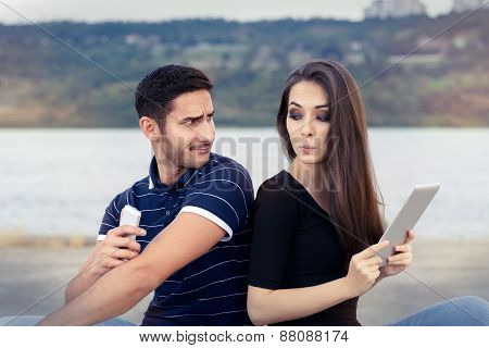 Secretive Couple with Tablet and Smartphone
