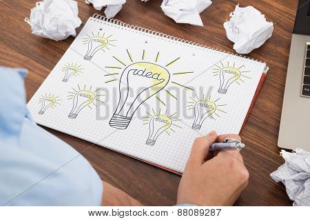 Businessperson Drawing Bulb On Book