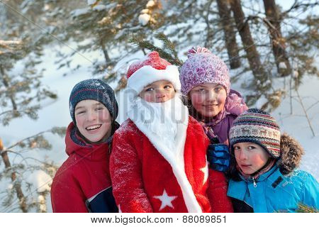 Portrait Of Children And Santa In Winter Forest