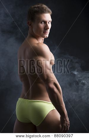 Handsome shirtless muscular man's back, turning around