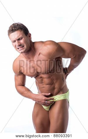Muscular handsome man holding his back in pain