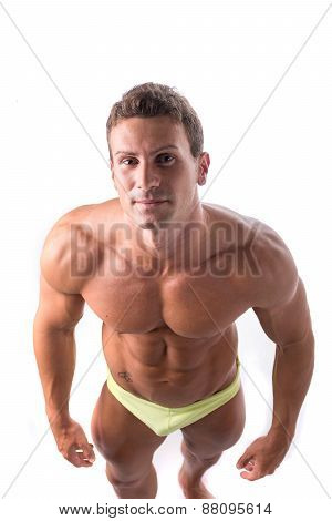Handsome shirtless bodybuilder shot from above, standing isolated