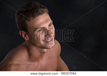 Head and shoulder shot of shirtless handsome young man smiling
