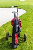 pic of golf bag  - a golf bag full of clubs near a sand trap bunker - JPG