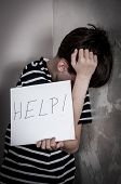 stock photo of scared  - Scared and abused young boy holding the paper with handwritten help sign. Low key ** Note: Soft Focus at 100%, best at smaller sizes - JPG