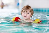 foto of floaties  - Active little toddler boy with swimmies learning to swim in an indoor pool - JPG