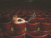 stock photo of cinema auditorium  - A young woman is talking on her phone in an auditorium - JPG