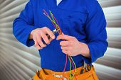 foto of pliers  - Electrician cutting wire with pliers against grey shutters - JPG