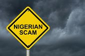 picture of warning-signs  - Nigerian Scam Warning Sign Yellow warning road sign with word Nigerian Scam with stormy sky background - JPG