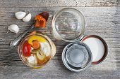 foto of pickled vegetables  - Home preserving mixed vegetables by pickling in glass canning jars - JPG