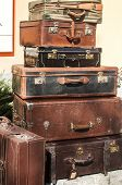 pic of old suitcase  - Old vintage retro used leather suitcases stacked and placed one on another in house backyard - JPG