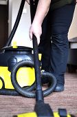 stock photo of maids  - Maid cleaning the carpet with vacuum cleaner  - JPG