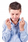 stock photo of fingers crossed  - portrait photograph of a child fingers crossed on a white background - JPG