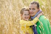 stock photo of bonding  - Caucasian mother and daughter hugging smiling and sharing a tender bonding moment amongst meadow grass - JPG