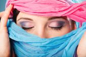 image of burka  - Young woman makeup on eyes hiden her face with multicolored shawl blue background - JPG