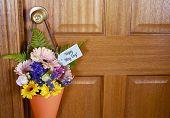 stock photo of door-handle  - Happy May Day traditional gift of Spring flowers in orange cone hanging from door handle on wooden door - JPG