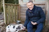 foto of pig  - Mature Man Feeding Pet Micro Pig - JPG
