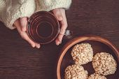 stock photo of crispy rice  - Woman wearing white woollen sweater holding cup of black teaand rice crispy balls in bowl on brown wooden background - JPG