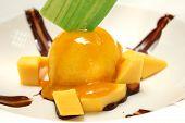 stock photo of mango  - Scoop of homemade mango ice cream with fresh mangos - JPG