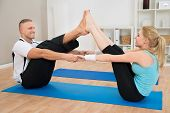 stock photo of legs apart  - Happy Young Couple Doing Exercise At Home - JPG