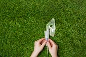 stock photo of asthma  - Asthma allergy inhaler sprayer over green grass - JPG
