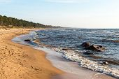 image of shoreline  - Shoreline of Baltic sea beach with rocks and sand dunes under clouds - JPG