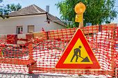 stock photo of flashing  - Construction site is protected by several traffic signs and orange fence with flashing beacon lights for safety - JPG