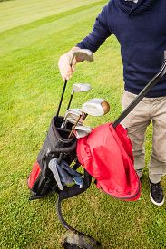 pic of golf bag  - a golf player playing on a beautiful golf course and a golf bag full of golf clubs - JPG