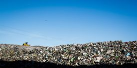 picture of ecology  - Landfill with bulldozer working against beautiful blue sky full of sea birds - JPG
