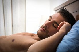 picture of laying-in-bed  - Handsome shirtless athletic young man laying in bed with eyes closed - JPG