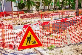 stock photo of safety barrier  - Construction site is protected by several signs and orange fence for safety - JPG