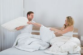 picture of pillow-fight  - Happy Couple Fighting Together With Pillows On Bed - JPG