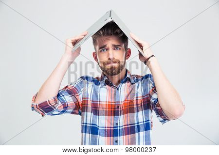 Casual man holding laptop on his head like roof of house isolated on a white background. Looking at camera