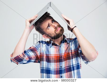 Young man holding laptop on his head like roof of house isolated on a white background. Looking up