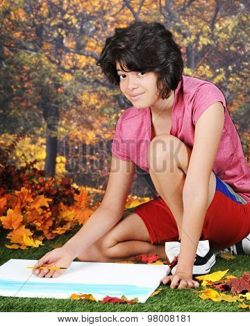 A pretty young teen looking up from her painting as she kneels in a park a warm fall day.