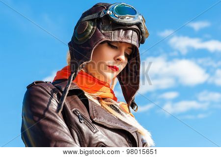 sadness woman in aviator helmet on the sky background