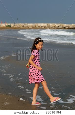 Little Girl With Pink Dress With Small Black Hearts Of The Beach In Summer